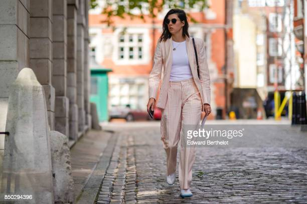 A guest wears sunglasses a pink blazer jacket pink pants a white top outside Simone Rocha during London Fashion Week September 2017 on September 16...