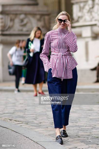 A guest wears sunglasses a red gingham top navy blue baggy pants black moccasins outside Margiela during Paris Fashion Week Womenswear Spring/Summer...