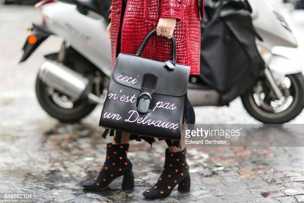 A guest wears sunglasses a red leather jacket with red fur a black fringed dress a Delvaux bag 'Ceci n'est pas un Delvaux' fishnet tights and black...