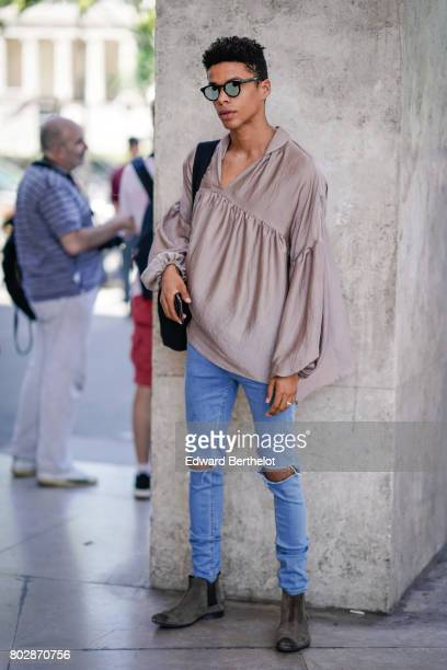 A guest wears sunglasses a silk top blue ripped jeans suede shoes outside the 22/4 Hommes show during Paris Fashion Week Menswear Spring/Summer 2018...