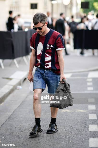 A guest wears sunglasses a striped top blue denim shorts black socks black leather shoes outside the Valentino show during Paris Fashion Week...