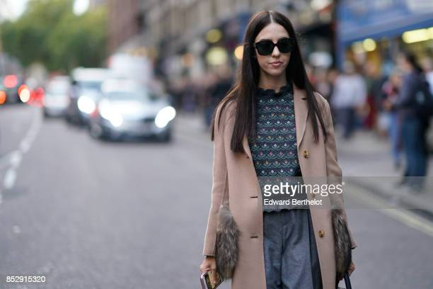 A guest wears sunglasses a trench coat a pull over flare pants during London Fashion Week September 2017 on September 16 2017 in London England