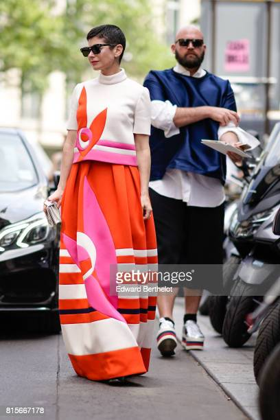A guest wears sunglasses a white and orange turtleneck top an orange ruffle dress with white stripes outside the Elie Saab show during Paris Fashion...