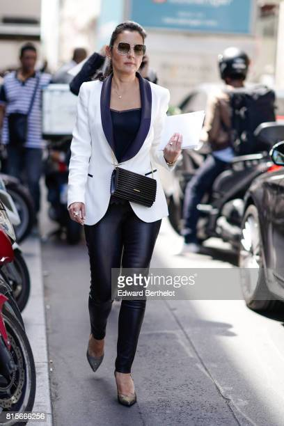 A guest wears sunglasses a white blazer jacket a black top black tight pants heels a studded bag outside the Elie Saab show during Paris Fashion Week...