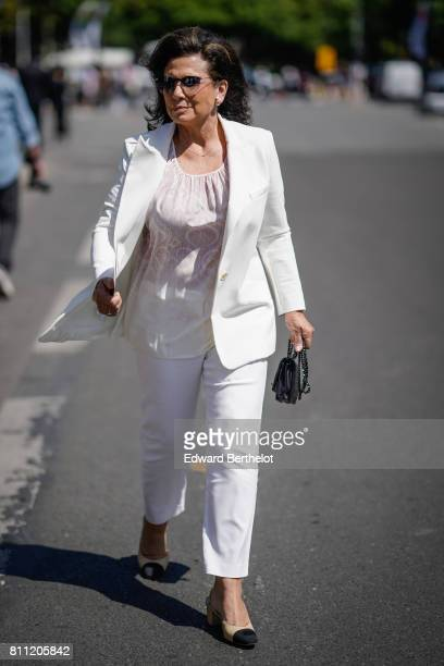 A guest wears sunglasses a white blazer jacket a white lace top white pants chanel shoes outside the Chanel show during Paris Fashion Week Haute...