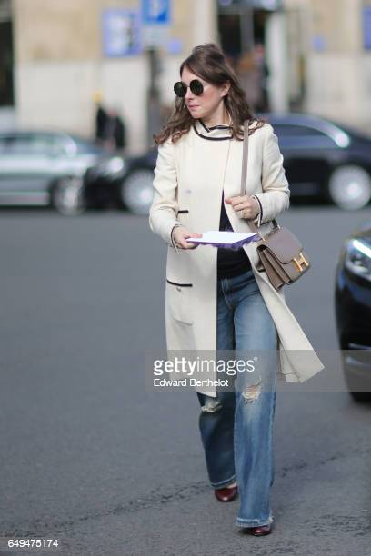 A guest wears sunglasses a white coat bllue ripped jeans a Hermes bag and brown shoes outside the Miu Miu show during Paris Fashion Week Womenswear...
