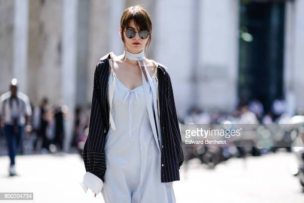 A guest wears sunglasses a white dress a jacket and blue shoes outside the Christian Dada show during Paris Fashion Week Menswear Spring/Summer 2018...