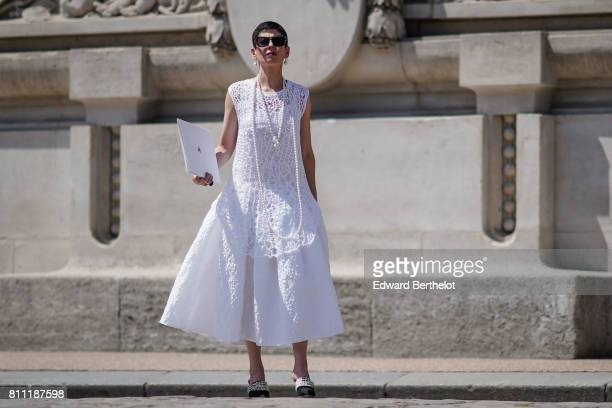A guest wears sunglasses a white lace dress shoes outside the Chanel show during Paris Fashion Week Haute Couture Fall/Winter 20172018 on July 4 2017...