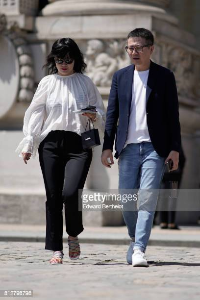A guest wears sunglasses a white lace mesh ruffle top black flare pants multicolor gladiator sandals a guest wears a blue blazer jacket a white top...