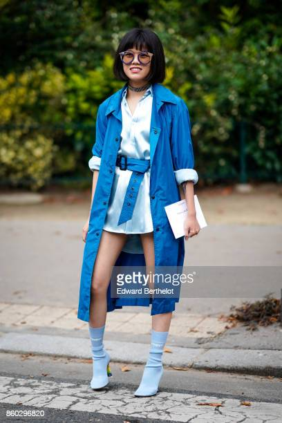 A guest wears sunglasses a white satin shirt a royal blue trenchcoat baby blue boots outside Lanvin during Paris Fashion Week Womenswear...