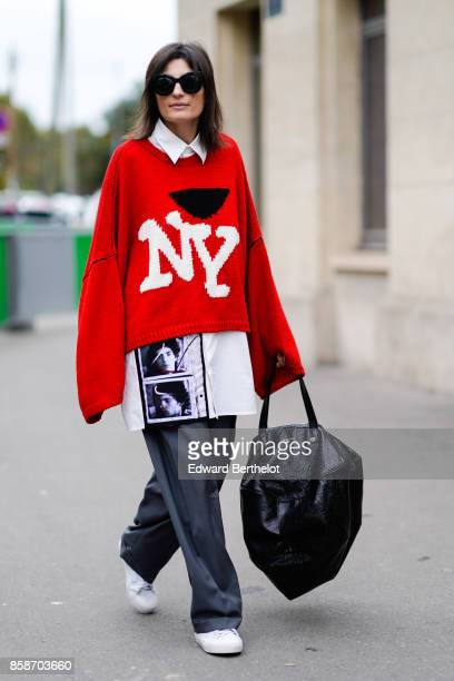 A guest wears sunglasses a white shirt with printed portraits a red oversizer pull over 'NY' large gray pants white sneakers a black large bag...