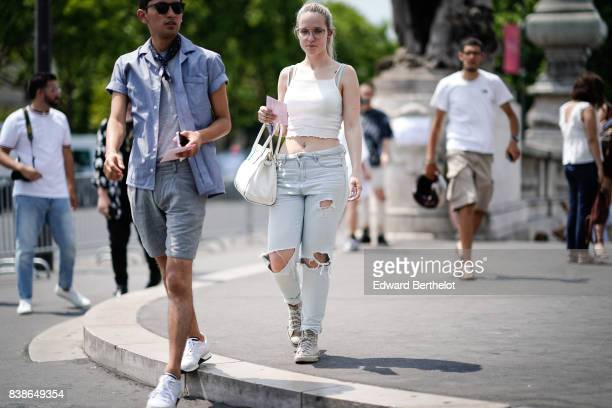 A guest wears sunglasses a white tank top ripped denim jeans pants outside the Icosae show during Paris Fashion Week Menswear Spring/Summer 2018 on...