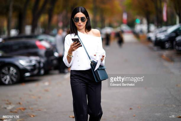 A guest wears sunglasses a white top black pants a blue bag outside Lanvin during Paris Fashion Week Womenswear Spring/Summer 2018 on September 27...