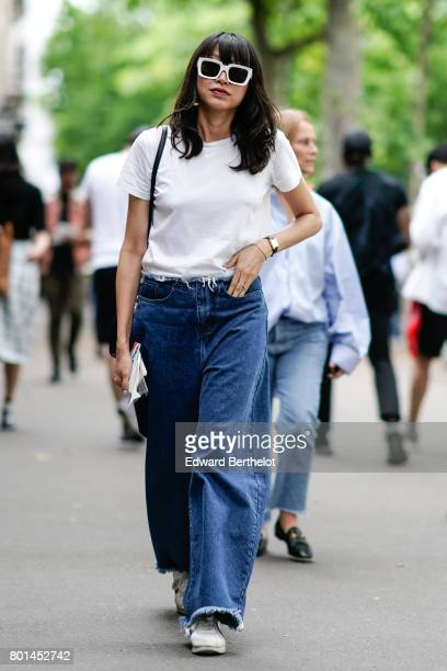 A guest wears sunglasses a white tshirt blue denim flared jeans outside the Paul Smith show during Paris Fashion Week Menswear Spring/Summer 2018 on...