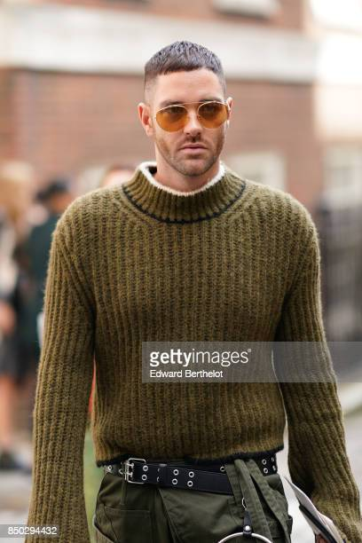 A guest wears sunglasses a wool pull over with long sleeves green cropped pants white socks outside Simone Rocha during London Fashion Week September...