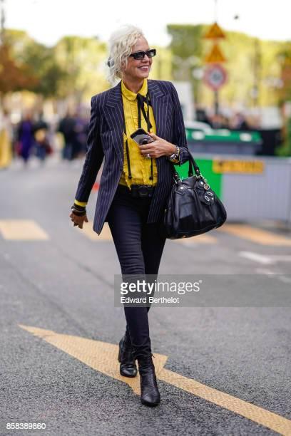 A guest wears sunglasses a yellow shirt a blazer jacket a tie black pants black shoes outside Moncler during Paris Fashion Week Womenswear...