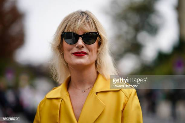 A guest wears sunglasses a yellow trenchcoat outside Lanvin during Paris Fashion Week Womenswear Spring/Summer 2018 on September 27 2017 in Paris...