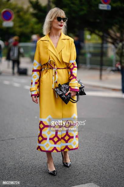 A guest wears sunglasses a yellow trenchcoat with red and white geometric prints a black patent leather geometric design bag black patent leather...