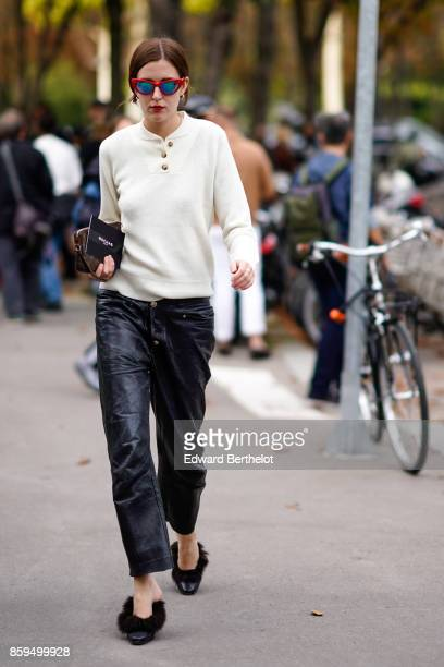 A guest wears sunglasses an ecru pullover with brass buttons black pants black highheeled slippers with black furoutside the Rochas show during Paris...