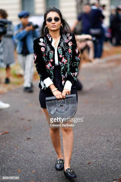 A guest wears sunglasses black embroidered jacket bamboo black bag and black moccasins outside Manish Arora during Paris Fashion Week Womenswear...
