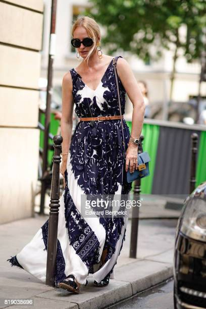 A guest wears sunglasses earrings a watch a blue bag and a dress with prints outside the Elie Saab show during Paris Fashion Week Haute Couture...