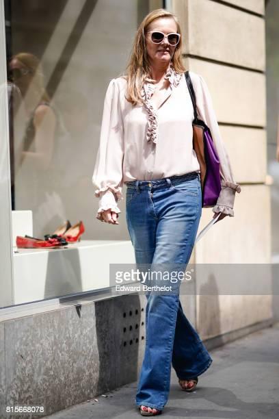 A guest wears white sunglasses a pink top blue denim flare jeans pants a purple bag outside the Elie Saab show during Paris Fashion Week Haute...