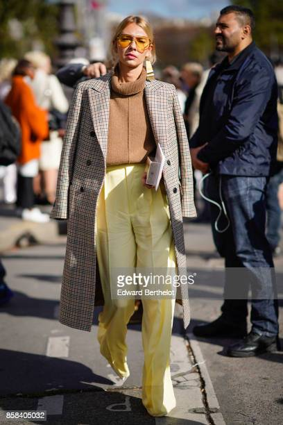 A guest wears yellow clear sunglasses a tartan trench coat a turtleneck brown pull over yellow pants outside Chanel during Paris Fashion Week...