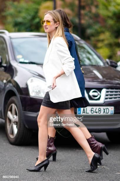 A guest wears yellow sunglasses a white jacket a black mini skirt black shoes outside Lanvin during Paris Fashion Week Womenswear Spring/Summer 2018...
