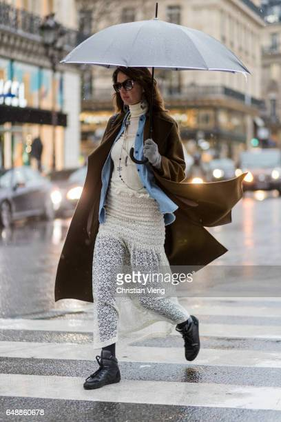 A guest with an umbrealla wearing a laced dress olive green coat outside Stella McCartney on March 6 2017 in Paris France