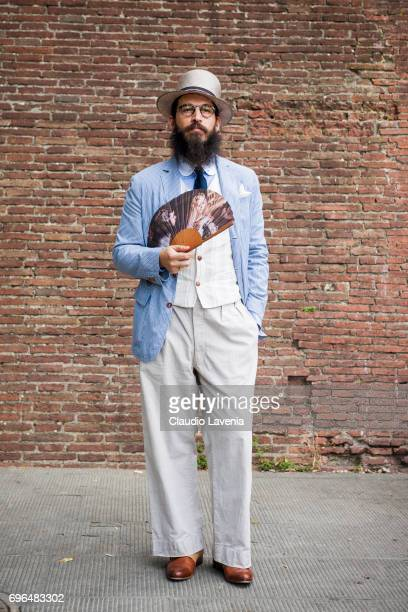 Guest with linen suit and fan is seen during Pitti Immagine Uomo 92 at Fortezza Da Basso on June 15 2017 in Florence Italy