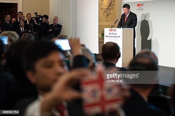 Guests and delegates take photos and videos as Chinese President Xi Jinping delivers a speech at the UKChina Business Summit in Mansion House central...