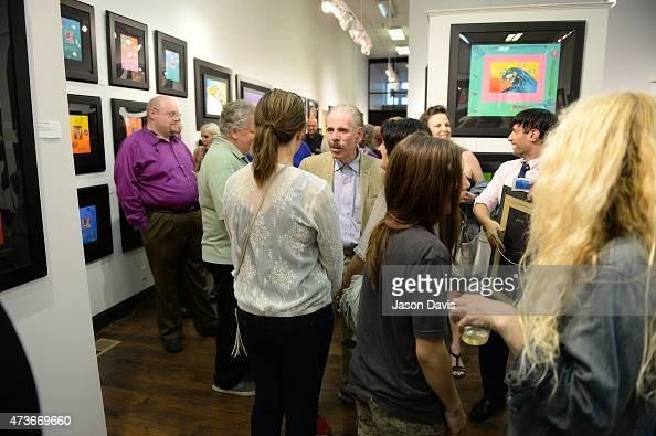 Guests and fans speak with Artist Peter Max during his 19602015 Retrospective at Music City Fine Art on May 16 2015 in Nashville Tennessee