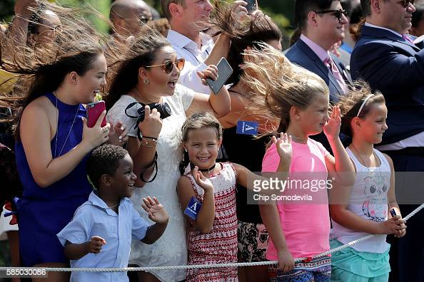Guests are blown by the wind created by the Marine One helicopter as US President Barack Obama departs the White House on the South Lawn August 1...