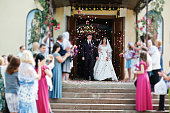 Guests are greeted wedding couple with petals of roses at exit from church.