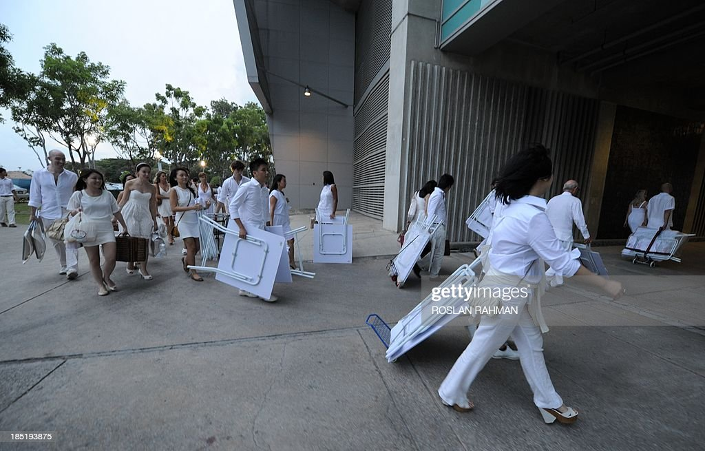 Guests arrive at Marina Barrage during the annual Diner en Blanc on October 18, 2013 in Singapore, the worlds only viral culinary event, a chic secret pop-up style picnic imported from France. More than 2,400 guests turned up to participate in Singapores second edition of Dîner en Blanc.