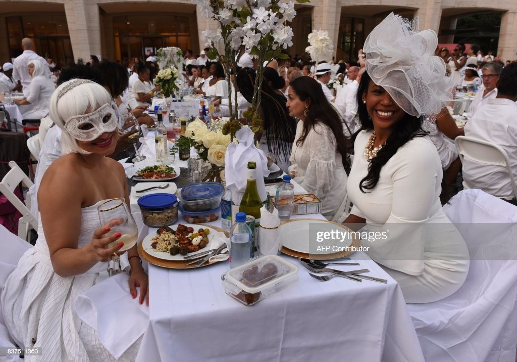 Guests attend the annual New York City Diner en Blanc, August 22, 2017 held this year at the plaza at Lincoln Center. The Diner en Blanc, the worlds only viral culinary event, a chic secret pop-up style picnic from France, the outdoor site -- always a landmark location -- is revealed at the last-minute. Guests are asked to dress entirely in elegant white, bring a picnic basket of food, fine china and silverware, white tablecloths, table and chairs. /
