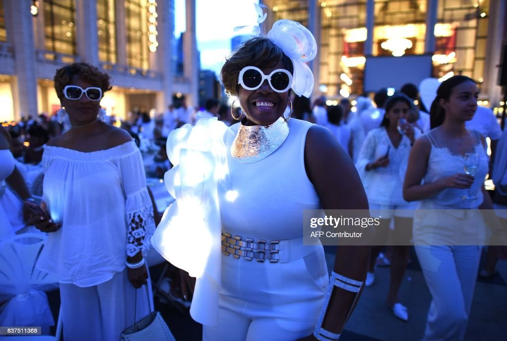 TOPSHOT - Guests attend the annual New York City Diner en Blanc, August 22, 2017 held this year at the plaza at Lincoln Center. The Diner en Blanc, the worlds only viral culinary event, a chic secret pop-up style picnic from France, the outdoor site -- always a landmark location -- is revealed at the last-minute. Guests are asked to dress entirely in elegant white, bring a picnic basket of food, fine china and silverware, white tablecloths, table and chairs. /