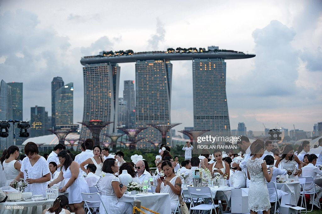 Guests attend the Marina Barrage during the annual Diner en Blanc, the worlds only viral culinary event, a chic secret pop-up style picnic imported from France, in Singapore on October 18, 2013. More than 2,400 guests turned up to participate in Singapores second edition of Dîner en Blanc.