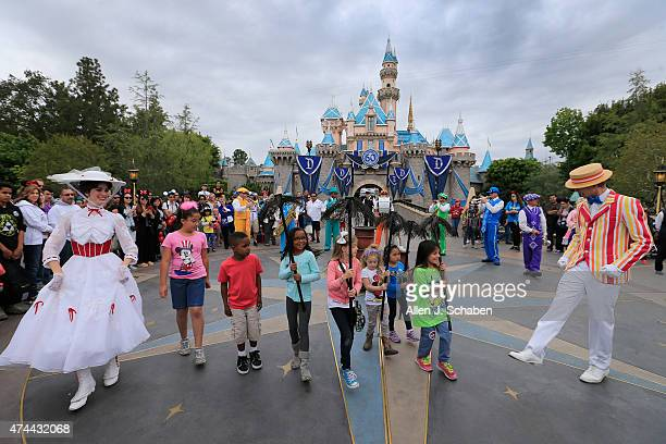 Guests dance with Disney characters Mary Poppins and Bert and the Pearly Band in front of Sleeping Beauty Castle during Disneyland's 24hour event to...