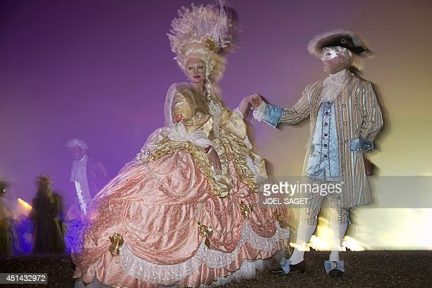 Guests dressed in as Louis XVI of France and Queen Marie Antoinette pose on June 28 2014 during the 2014 Great Masked Ball held in the gardens of the...