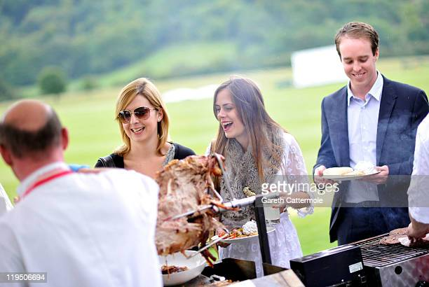 Guests enjoy a hog roast lunch during an exclusive cricket day in the idyllic surroundings of the Getty family estate at Wormsley Buckinghamshire on...