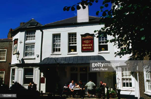 Guests enjoying drink outside Holly Bush Inn at Hampstead.