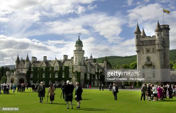 Guests gather on the lawn at Balmoral castle Scotland during a visit by Britain's Queen Elizabeth II The Queen watched the Highland Band of the...