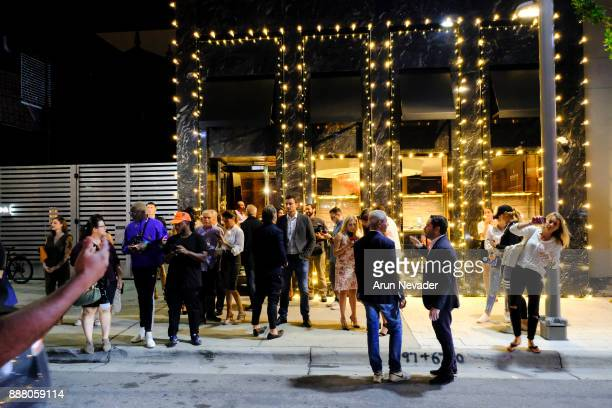Guests gather outside Vagu during the cocktail reception at Vagu on December 7 2017 in Miami Florida