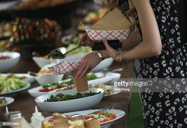 Guests get food from a buffet table during a Congressional Picnic at the White House June 22 2017 in Washington DC President Trump and the first lady...