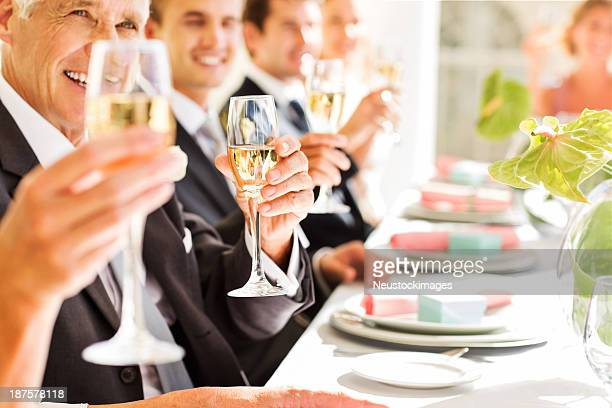 Guests Holding Champagne Flutes While Sitting At Table