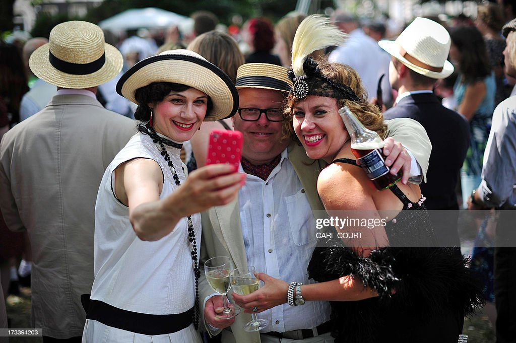 Guests in period costumes take a picture with a mobile phone during 'The Chap Olympiad' in central London on July 13, 2013. The Chap Olympiad is a light-hearted social sporting event aimed at revisiting the fashions and pastimes of the polite aspects of 1920's to 1950's England.