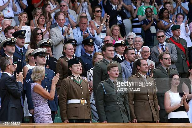Guests in the royal box on centre court give a standing ovation to members of the armed forces before the start of the men's singles third round...