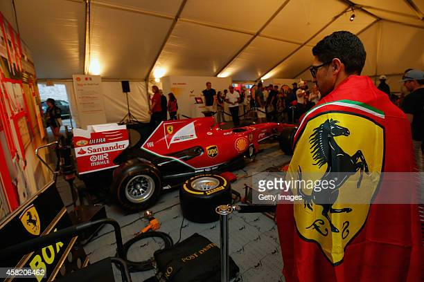 Guests inspect a Ferrari F1 show car on display at the Shell Fan Festival during previews ahead of the United States Formula One Grand Prix on...