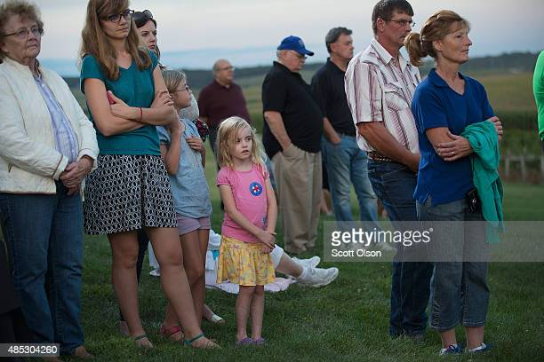 Guests listen as Democratic presidential candidate Hillary Clinton speaks during a campaign event at Tabor Home Vineyards and Winery on August 26...